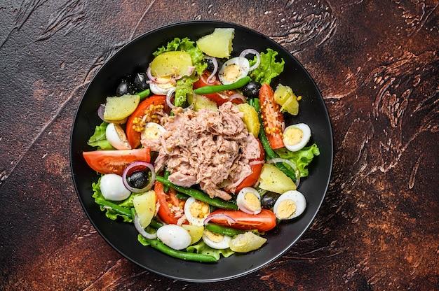 참치, 녹두, 토마토, 계란, 감자, 블랙 올리브를 접시에 담은 건강하고 풍성한 샐러드. 어두운 배경입니다. 평면도.