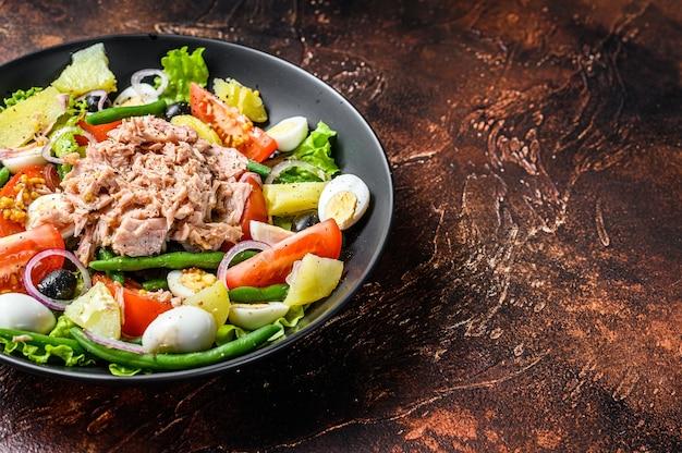 ツナ、インゲン、トマト、卵、ジャガイモ、ブラック オリーブを皿に盛り付けたヘルシーなボリュームたっぷりのサラダ。暗い背景。