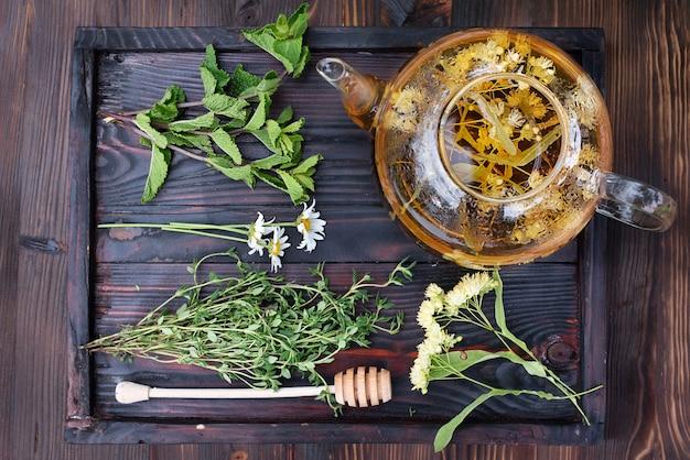 Концепция здорового травяного чая, стеклянный чайник с липовым чаем, мятой, тимьяном и веточками ромашки на деревянном подносе, крупным планом.
