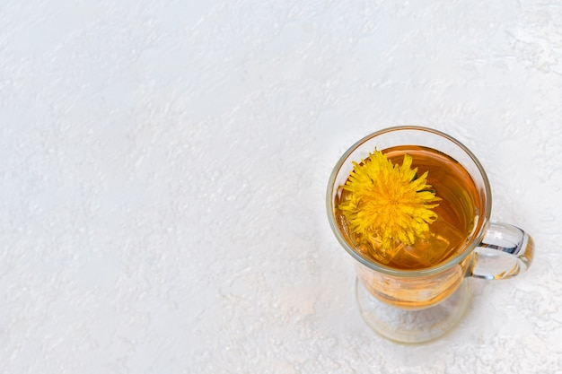 Healthy herbal tea with dandelions in a glass cup, ice and yellow dandelion flower inside on a white background, top view, copy space, close-up. summer refreshing drink, thirst quencher in hot weather