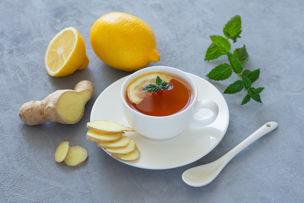 Healthy herbal tea with fresh sliced ginger, lemon and mint on stone background