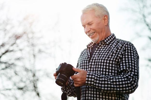 健康的な趣味。笑顔でカメラを使用してゲイの年配の男性のローアングル