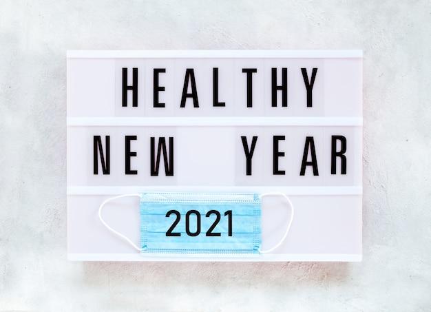 코로나 바이러스 covid-19 시간 동안 건강한 휴일 새해 2021 개념 배너. 문자로 일회용 보호 얼굴 마스크의 상위 뷰