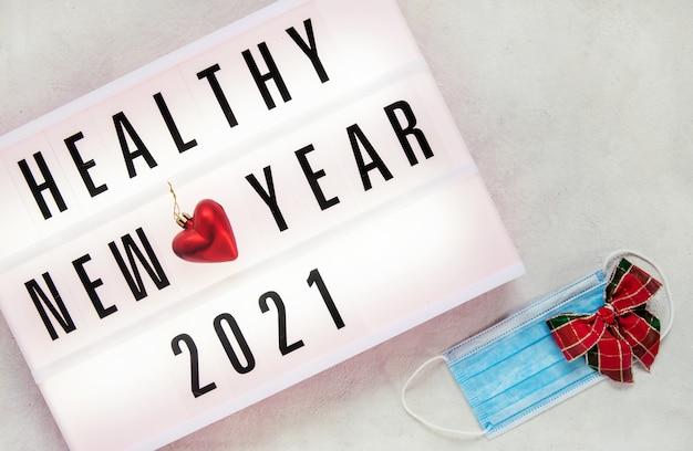 코로나 바이러스 covid-19 시간 동안 건강한 휴일 새해 개념 배너. 문자로 일회용 보호 얼굴 마스크의 상위 뷰