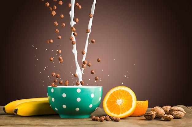 떨어지는 뮤즐리와 우유, 사과, 신선한 과일, 호두로 구성된 건강한 가정식 아침 식사. 신선하고 얇게 썬 오렌지와 함께 제공됩니다.
