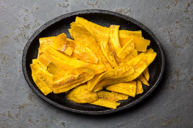 Healthy homemade banana plantain chips on black plate