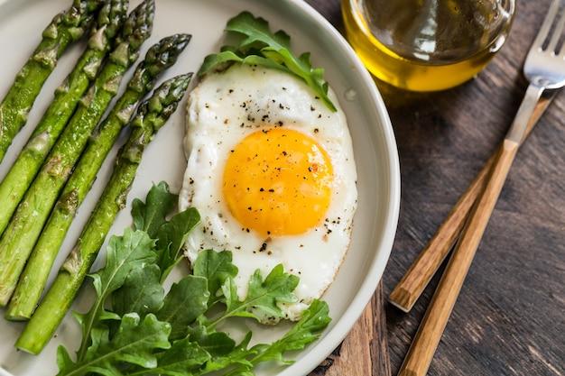 Здоровый домашний завтрак со спаржей, жареным яйцом и рукколой. концепция карантина здорового питания. кето диета