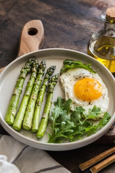 Healthy homemade breakfast with asparagus, fried egg and arugula. quarantine healthy eating concept. keto diet