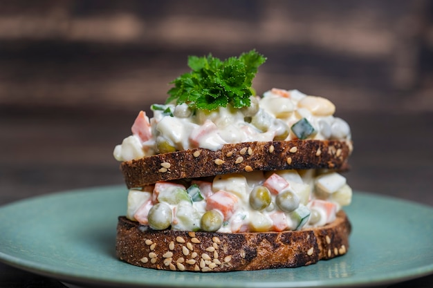 Здоровый домашний двойной бутерброд с салатом оливье в тарелке, готовый к употреблению, заделывают. украинская кухня