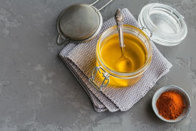 건강 수제 버터 기름 또는 회색 콘크리트 배경에 항아리와 파프리카 가루에 명확히 버터. 건강한 ayurveda 음식 개념.