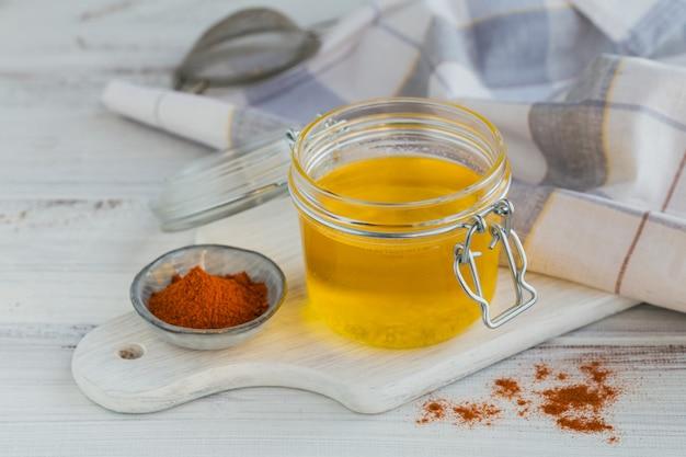 건강 한 수 제 버터 기름 또는 흰색 나무 테이블에 항아리와 파프리카 가루에 명확히 버터. 건강한 ayurveda 음식 개념.