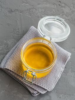 회색의 항아리에 건강한 수제 기 또는 정화 버터. 건강한 ayurveda 음식 개념.