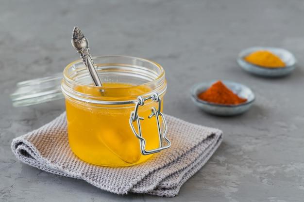 회색 콘크리트 배경에 항아리, 심황 및 파프리카 가루에 건강 수제 버터 기름 또는 정화 버터. 건강한 ayurveda 음식 개념.