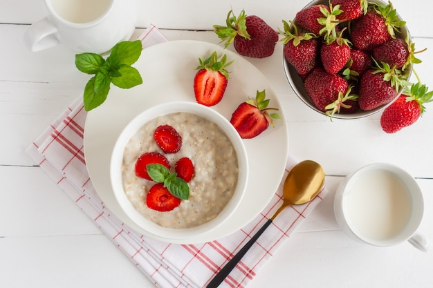Healthy homemade oatmeal with fresh strawberries on white marble background. top view.