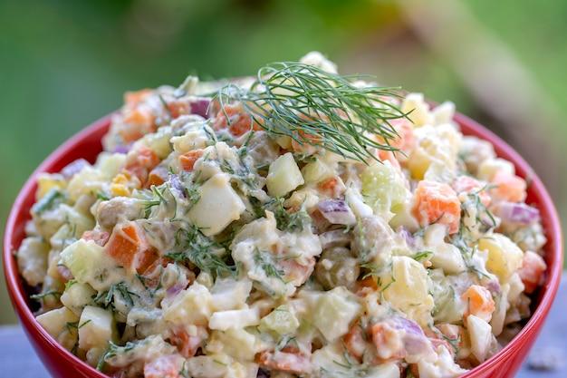 Здоровый домашний русский традиционный салат оливье готов к употреблению, крупным планом, вид сверху