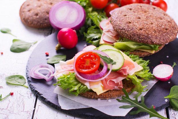 Healthy homemade rye burgers with fresh vegetables, cheese and ham on white wooden background.