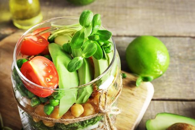 木製の背景にキノア、野菜、ハーブとガラスの瓶でヘルシーな自家製サラダ。ビーガンフードのコンセプト。