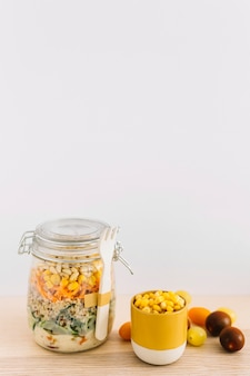 Healthy homemade salad in mason jar and corn seeds in cup on wooden table