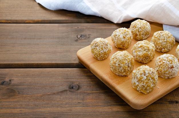 ココナッツのドライフルーツとナッツの健康的な自家製の甘いエネルギーボール。ドライアプリコット、レーズン、イチジク、デート、アーモンド、クルミ、ヘーゼルナッツ、蜂蜜の組成。