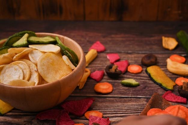 木製の背景に健康的な自家製野菜チップス。