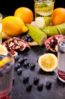 暗いヴィンテージの木製の背景に果物や野菜から健康的な自家製ビタミン水