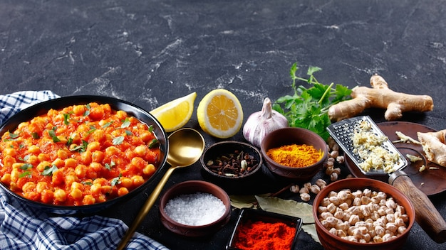 Healthy indian chana masala or chickpea curry with ingredients on a dark concrete background: