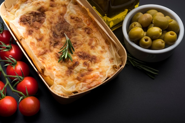 Healthy ingredient with tasty lasagna over black background