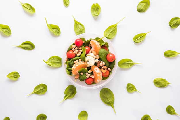 Healthy ingredients in bowl surrounded by leaves arranged on white backdrop