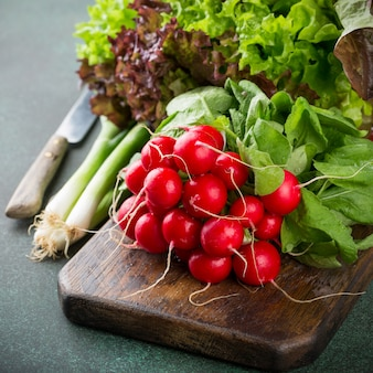 Healthy ingredients for salad on old wooden cutting board.