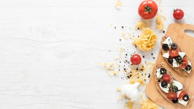 Healthy italian bread sandwich on chopping board with spices; tomato and tagliatelle pasta