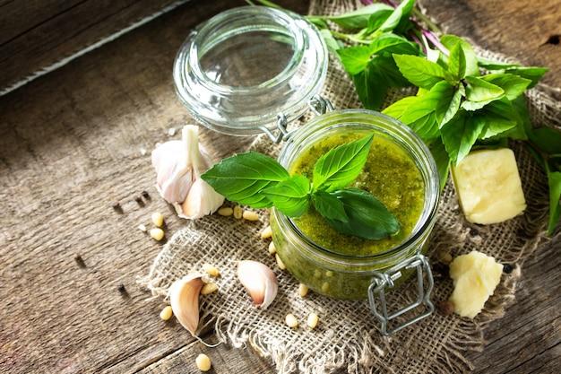 Здоровая итальянская кухня зеленый соус песто с ингредиентами на деревенском деревянном столе копирование пространства