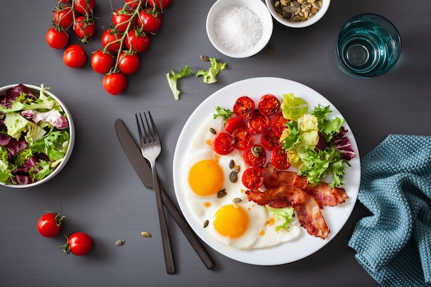 Healthy keto diet breakfast: egg, tomatoes, salad leaves and bacon