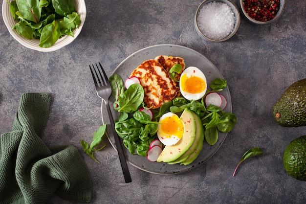 Healthy keto paleo diet breakfast: boiled egg, avocado, halloumi cheese, salad leaves