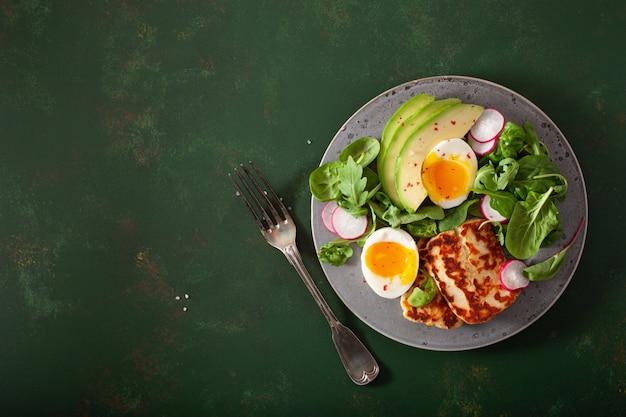 건강한 케토 팔 레오 다이어트 아침 식사 : 삶은 계란, 아보카도, 할루 미 치즈, 샐러드 잎