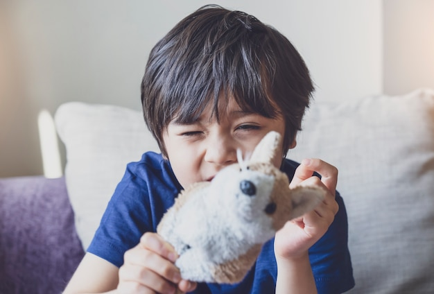 Healthy kid portrait playing with dog toy with funny face, candid shot cute child boy relaxing stay at home during covid lock down.positive children concept,social distancing