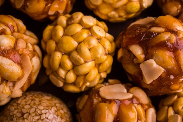 구운 땅콩, 참깨, 스플릿 daliya와 jaaggery를 사용한 건강한 laddoo는 나무 접시에 제공되며 선별적인 초점을 맞춥니다.