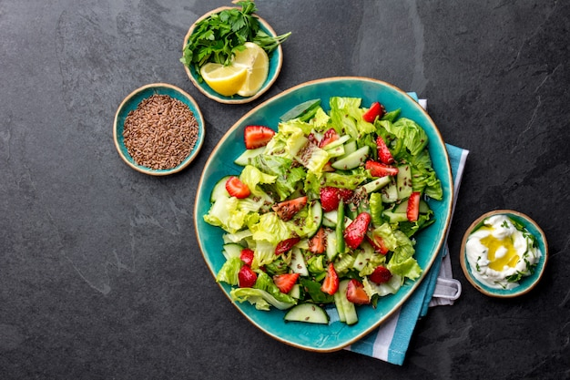 Healthy lettuce strawberry salad with linen seeds on blue plate top view