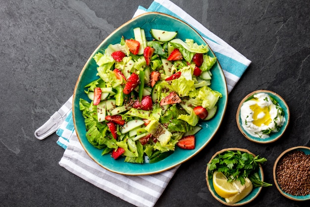 Healthy lettuce strawberry salad with linseeds on blue plate
