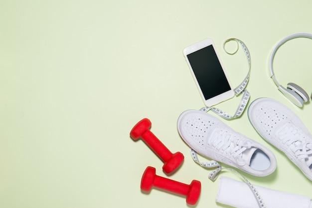 健康的な生活の概念。パステルカラーの背景にスニーカー、ヘッドフォン、ダンベル、スマートフォン。