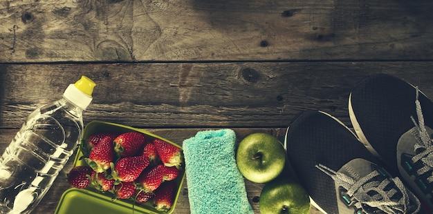 건강한 생활 스포츠 개념입니다. 사과, 수건 및 나무 배경에 물 병 운동 화. 공간을 복사하십시오.