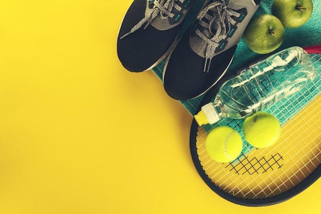 健康的なスポーツスポーツの概念。テニスボール、タオル、明るい黄色の背景に水のボトルスニーカー。スペースをコピーします。