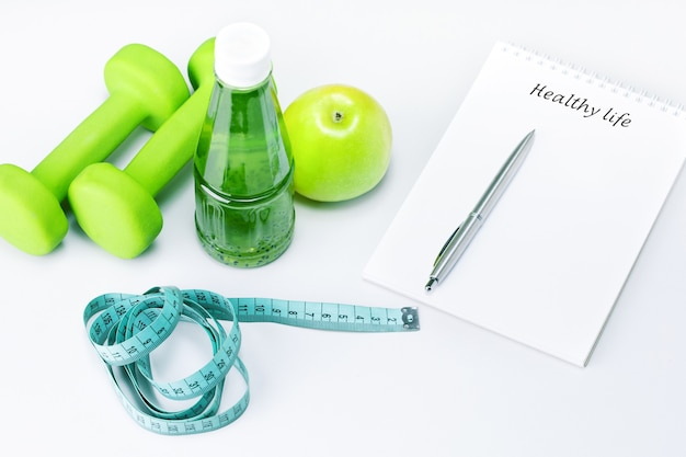 Healthy life written in a white notebook near the apple, bottle of juice and sport equipment on a white table. healthy life style food fitness concept