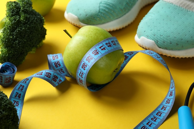 Healthy lifestyle accessories on yellow background, close up
