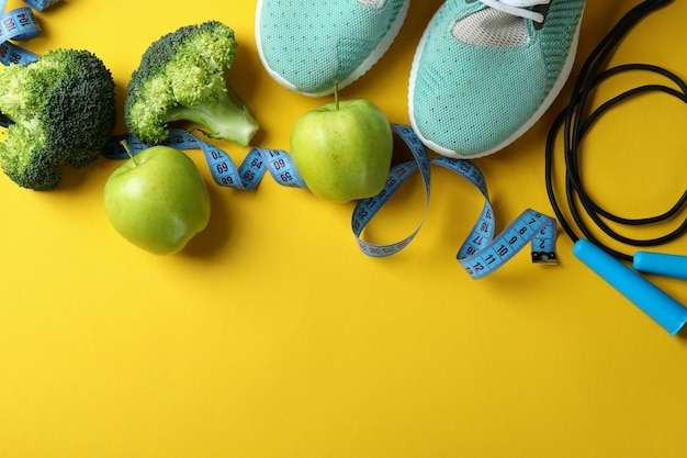 Healthy lifestyle accessories on yellow background, space for text