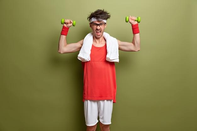 Здоровый образ жизни и тренировки в тренажерном зале. решительный мужчина поднимает гантели для сильных мышц, прилагает все усилия для достижения положительного результата, одет в спортивную одежду с полотенцем на шее, изолирован на зеленом