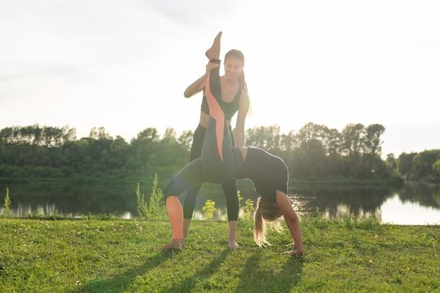 Концепция здорового образа жизни и гармонии - молодые девушки занимаются йогой на открытом воздухе