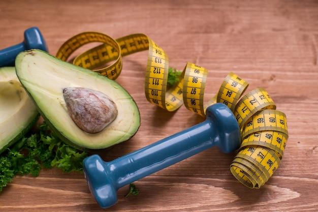 Здоровый образ жизни и здоровые привычки зеленый авокадо и гантели спорт и правильное питание