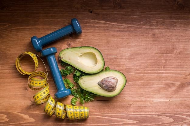 健康的なライフスタイルと健康的な習慣の概念グリーンアボカドとダンベルスポーツと適切な食事
