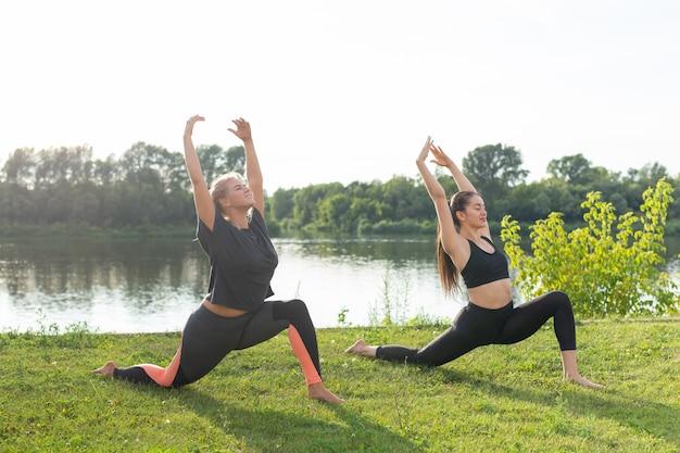 Концепция здорового образа жизни и людей - гибкие женщины занимаются йогой в летнем парке