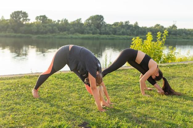 健康的なライフスタイルと人々の概念-サマーパークでヨガをしている柔軟な女性